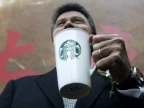 Starbucks Coffee International President Culver poses with a cup of Starbucks coffee with its new logo in Beijing