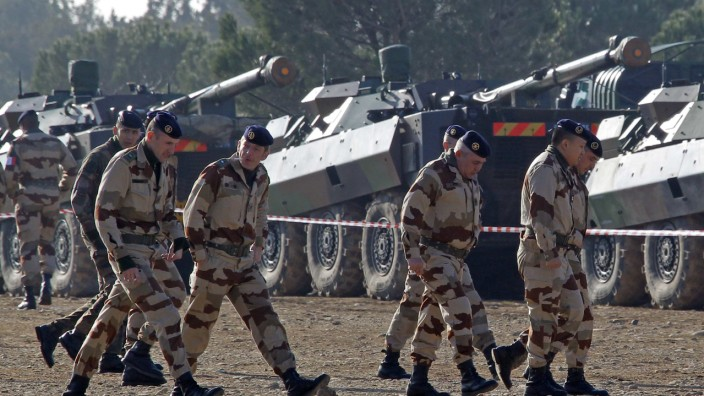 French soldiers, who prepare for their departure for Mali, walk past armoured vehicles at the military base of Miramas