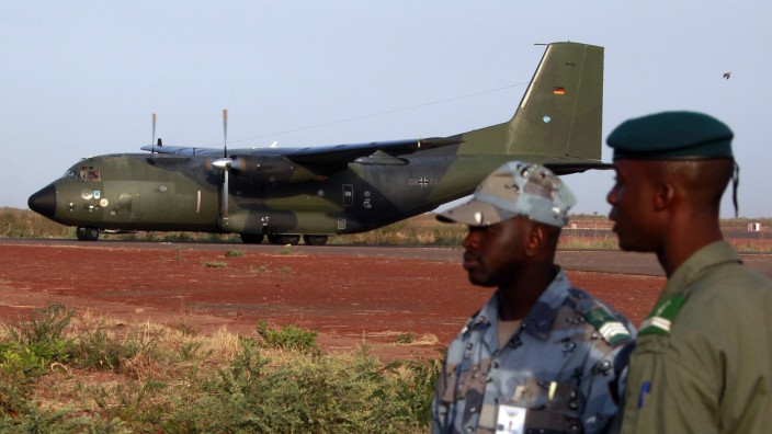 Malian soldiers stand guard while the first German military transall C-160 cargo lands in Bamako airport