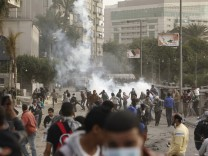 Protesters against Egypt's President Mursi run from tear gas released by riot police during clashes in Cairo