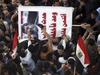 Protesters opposing Egyptian President Mohamed Mursi shout slogans and hit a poster of Mursi that reads 'If he speaks, he always lies' with shoes at Tahrir Square in Cairo