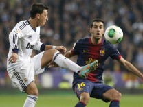 Real Madrid's Ozil fights for the ball with Barcelona's Busquets during their Spanish King's Cup semi final first leg soccer match in Madrid