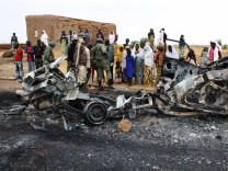 Residents look at the remains of vehicles which they said belonged to radical Islamist group MUJAO, after they were hit by French air strikes in the town of Gao