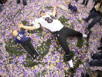 Baltimore Ravens Billy Bajema lies in the confetti on the field with his children as he celebrates in the NFL Super Bowl XLVII football game in New Orleans