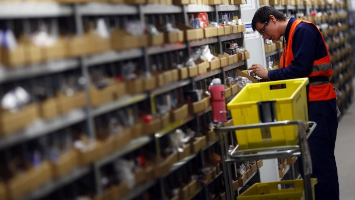 A worker collects items to pack into boxes at Amazon's logistics centre in Graben near Augsburg