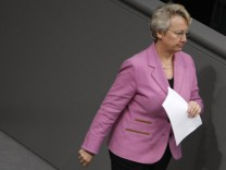 German Chancellor Merkel looks to German Education and Science Minister Schavan as she walks to podium in Bundestag in Berlin