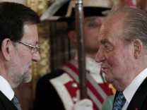 Spain's King Juan Carlos speaks to Spain's Prime Minister Mariano Rajoy during a diplomatic reception at the Royal Palace in Madrid