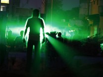 Anti-government protesters shout slogans while standing in front of laser beams emitted by riot police in the village of Diraz west of Manama