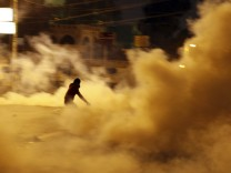A protester, who opposes Egyptian President Mohamed Mursi, is seen amidst teargas released by riot police during clashes in front of the presidential palace in Cairo