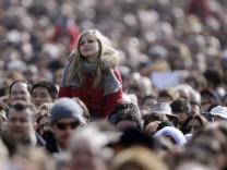 A girl looks on as Pope Benedict XVI leads the Sunday Angelus in Saint Peter's Square at the Vatican