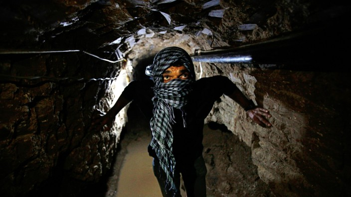 Palestinian works inside a smuggling tunnel flooded by Egyptian forces beneath the Egyptian-Gaza border in Rafah