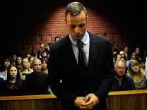 Oscar Pistorius stands in the dock ahead of court proceedings at the Pretoria magistrates court