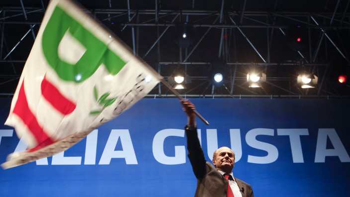 Supporters attend as Italy's Democratic Party leader Bersani waves a flag during his political rally in downtown Naples