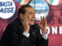 Italy's former Prime Minister Silvio Berlusconi gestures as he appears as a guest on the RAI television show Porta a Porta (Door to Door) in Rome