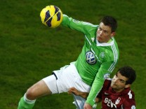 Alexander Madlung of Germany's first division Bundesliga club VfL Wolfsburg challenges Thomas Rathgeber of third division club Kickers Offenbach during their German soccer cup, DFB Pokal, quarter final match in Offenbach