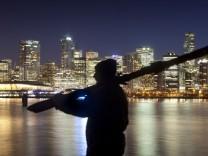 Mann trägt Ski vor der nächtlichen Kulisse von Vancouver