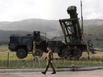 Soldiers of the German armed forces Bundeswehr stand next to the Patriot system before the arrival of Germany's Chancellor Angela Merkel at a Turkish military base in Kahramanmaras