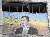 A picture of Syria's President Bashar al-Assad riddled with holes is seen on the facade of the police academy in Aleppo, after it was captured by Free Syrian Army fighters