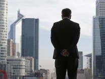 A businessman looks on as he stands under the Arche de la Defense in the financial district west of Paris