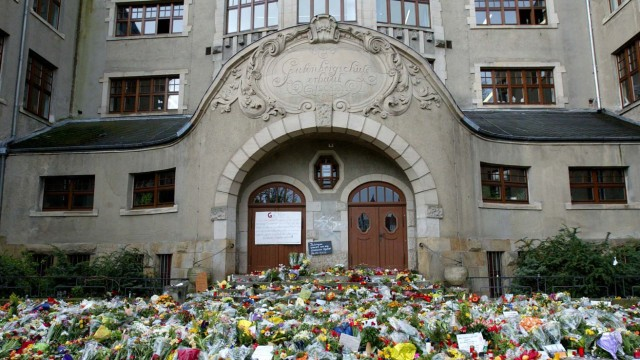 FLOWERS AND CANDLES ARE PLACED AT THE MAIN ENTRANCE OF THE GUTENBERG SECONDARY SCHOOL IN ERFURT