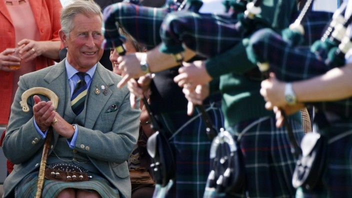 Britain's Prince Charles applauds as bagpipers walk past during the Mey Highland Games in Caithness, northern Scotland
