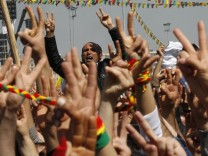 Demonstrators gesture and shout slogans during a gathering to celebrate Newroz in the southeastern Turkish city of Diyarbakir