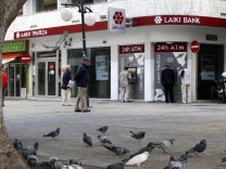 People withdraw money from the ATM of Laiki Bank in Nicosia