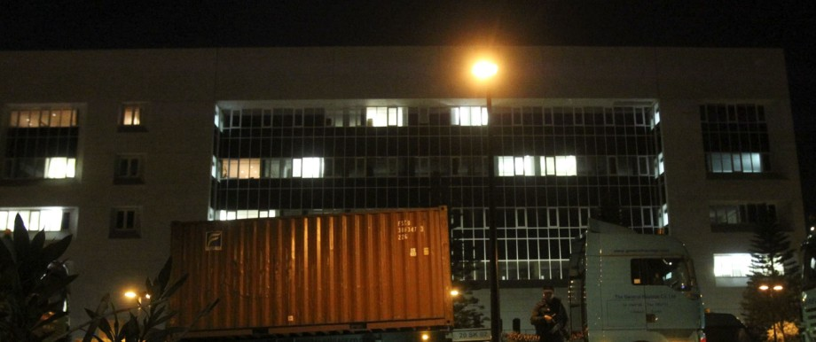 Policeman stands guard in front of trucks carrying containers at the Central Bank in Nicosia