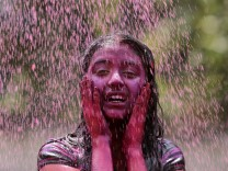 A girl is drenched with coloured water as part of Holi celebrations in the southern Indian city of Hyderabad