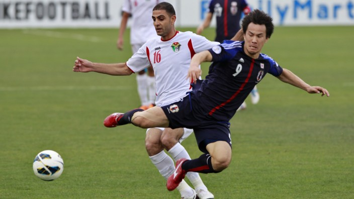 Japan's Okazaki fights for the ball against Jordan's Othman during their 2014 World Cup qualifying soccer match at King Abdullah stadium in Amman