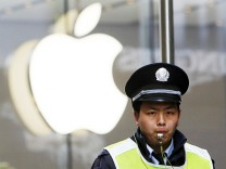 File photo of a security guard standing in front of an Apple store in Shanghai