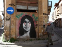 A man walks in front of a mural in central Nicosia