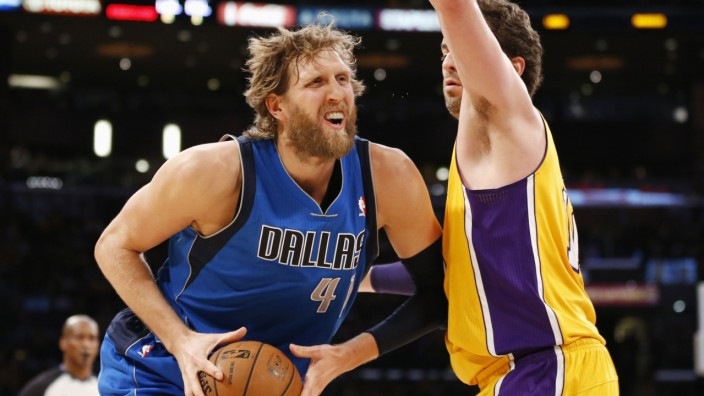 Dallas Mavericks' Dirk Nowitzki controls the ball as Los Angeles Lakers' Pau Gasol defends him during the first quarter of their NBA basketball game in Los Angeles