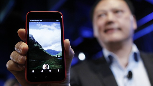 HTC CEO Peter Chou holds an HTC First phone showing the new app Facebook Home for Android