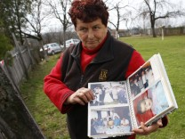 A local resident shows an album with photographs of people living in the village of Velika Ivanca