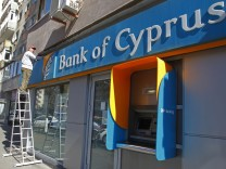 A worker paints a wall above a branch of Bank of Cyprus in Bucharest