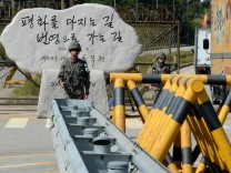 File photo of South Korean soldiers keeping watch as a South Korean truck carrying choco mochi cakes drives past the military fences in the demilitarised zone as the truck departs to the Kaesong Industrial Complex