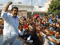 Acting Venezuelan President Maduro gestures to supporters as he leaves after voting for the successor to the late President Chavez, in Caracas