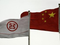 A flag printed with a logo of the Industrial & Commercial Bank of China flies along with a Chinese flag outside a branch in China's southern city of Shenzhen