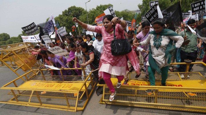 Supporters of India's main opposition BJP cross over a police barricade as they march towards residence of chief of India's ruling Congress party Sonia Gandhi during a protest rally in New Delhi