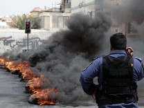 Riot police officer stands in front of a line of burning tyres in the early hours of morning in Manama