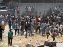 Garment workers throw pieces of bricks at police near the Rana Plaza building in Savar