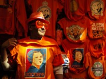 A man wearing shades displays a t-shirt depicting Dutch Queen Beatrix in a souvenirs shop in Amsterdam