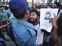 A relative argues with member of the police as he shows picture of garment worker, who has been missing, during a protest in Savar