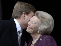 Princess Beatrix of Netherlands embraces his son Dutch King Willem-Alexander at the balcony of the Royal Palace in Amsterdam