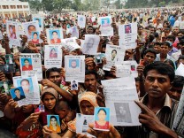 File picture shows relatives mourning as they show pictures of garment workers, who are believed to be trapped under the rubble of the collapsed Rana Plaza building, in Savar