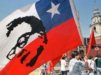 MAN WITH CHILEAN FLAG AND SALVADOR ALLENDES IMAGE