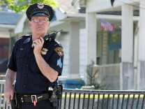 A Cleveland police officer stands guard outside the house where three women who vanished as teenagers about a decade ago were discovered alive, in Cleveland, Ohio