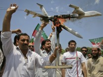 Activists of PTI hold up a burning mock drone aircraft during a rally against drone attacks in Peshawar