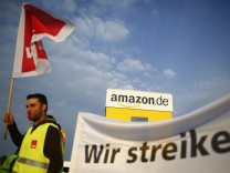 An employee of Amazon takes part in strike by German united services union Ver.di in front of Amazon warehouse in Bad Hersfeld
